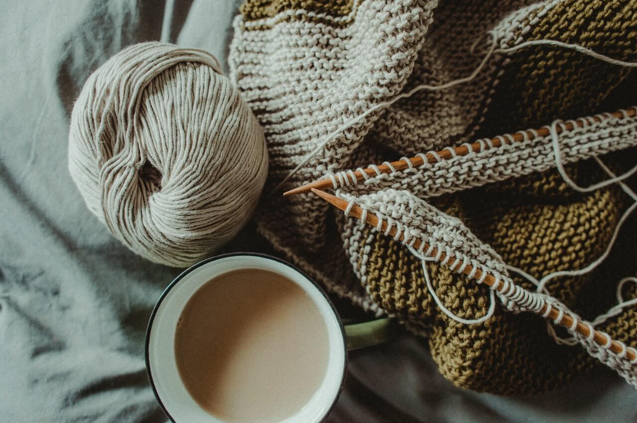 filiżanka kawy i przyrządy do robienia na drutach
